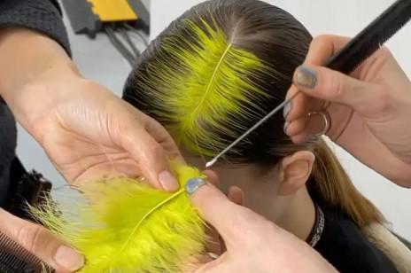 Kolorowe pióro zamiast przedziałka? To uczesanie wygląda jak bardziej wytworna wersja fryzury Billie Eilish. Jest idealne na sylwestra!
