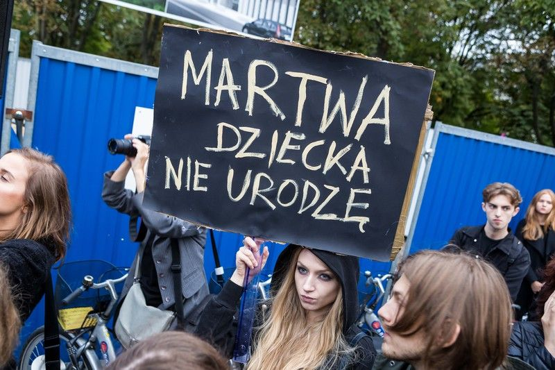 kobieta trzyma transparent z napisem Martwa dziecka nie urodzę
